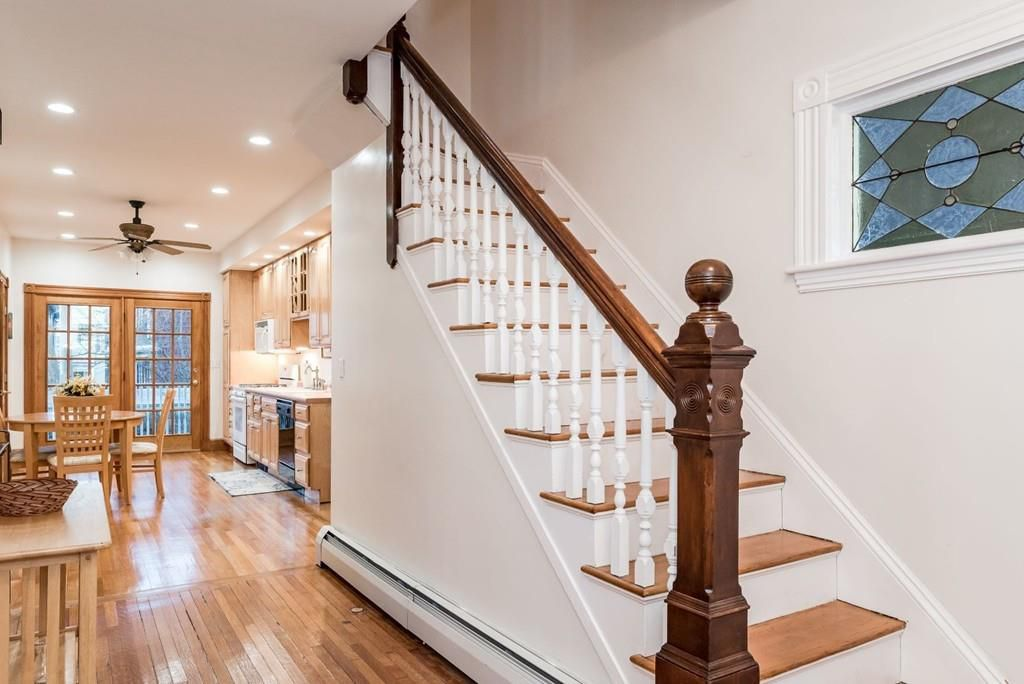 An entryway of a house, with stairs on one side and a passage to an open living room on the other.