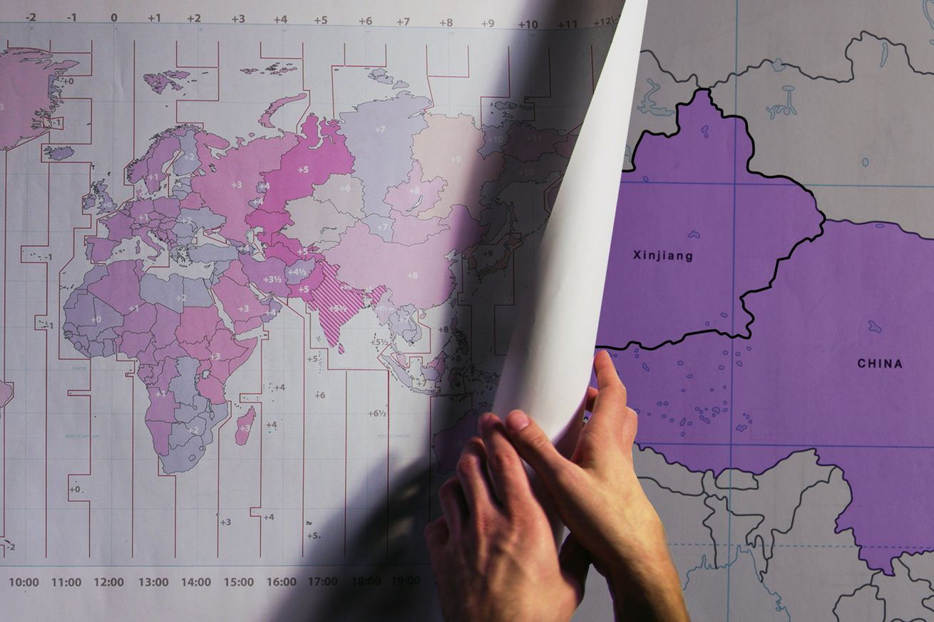 Hand rolls time zone map out onto table