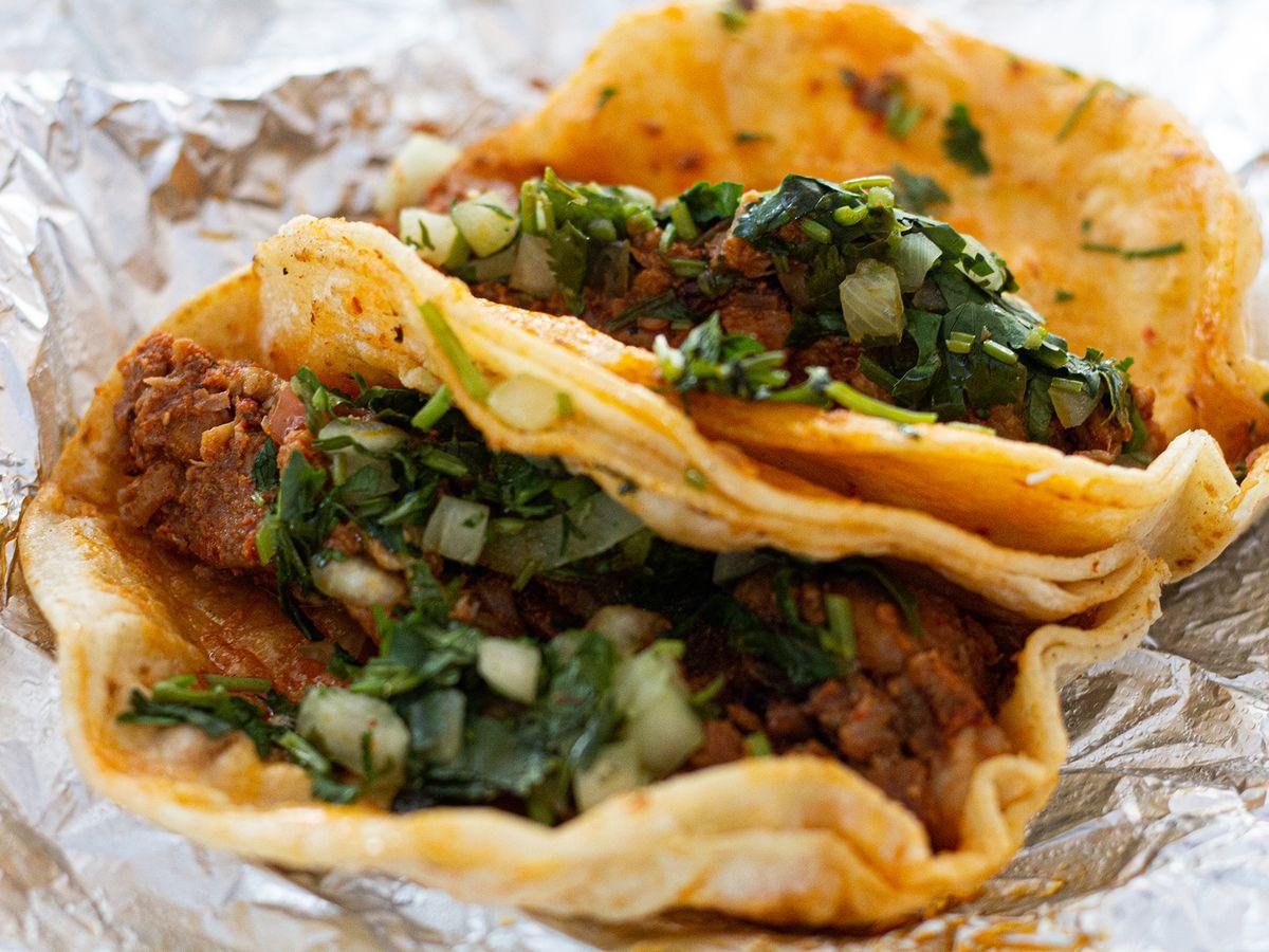 Two tacos al pastor swaddled by aluminum foil