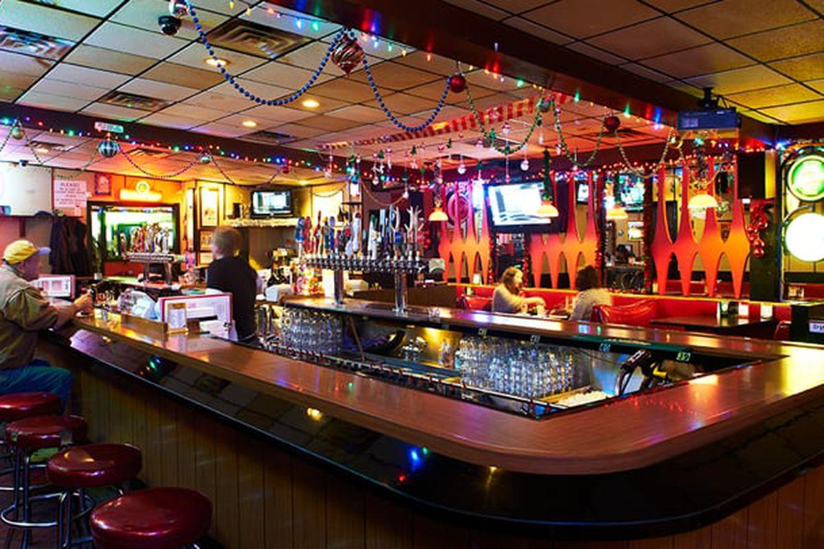 The dark round, laminate wood topped bar inside a dimly lit Liquor Lyle's