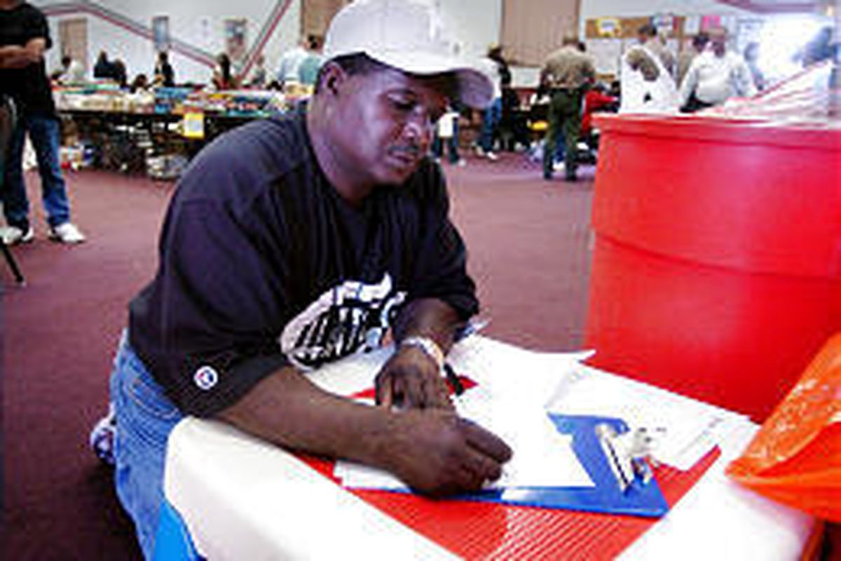 Hurricane evacuee Henry Barnes fills out an application for employment with UTA during a job fair at Camp Williams.