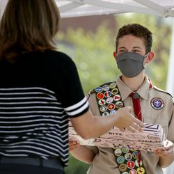 Anton Goodick, 14, receives a gift at the grand opening of the Mill Creek Elementary Food Pantry & Resource Center at the Millcreek school on Thursday, Sept. 17 2020. Anton built up the food pantries at both Mill Creek and James E. Moss Elementary as an Eagle Scout project.