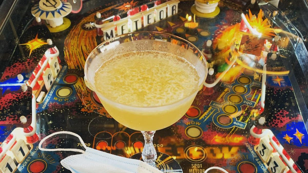 A martini glass with an icy yellow liquid sits on a vintage pinball machine with a blue, medical face mask in front of it