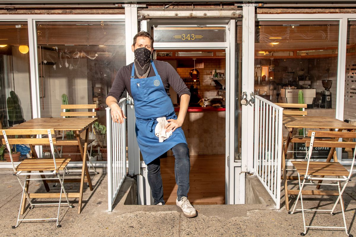 Matt Diaz, clad in a blue apron and a handkerchief face mask, stands in between two outdoor tables at the front of the entrance to For All Things Good
