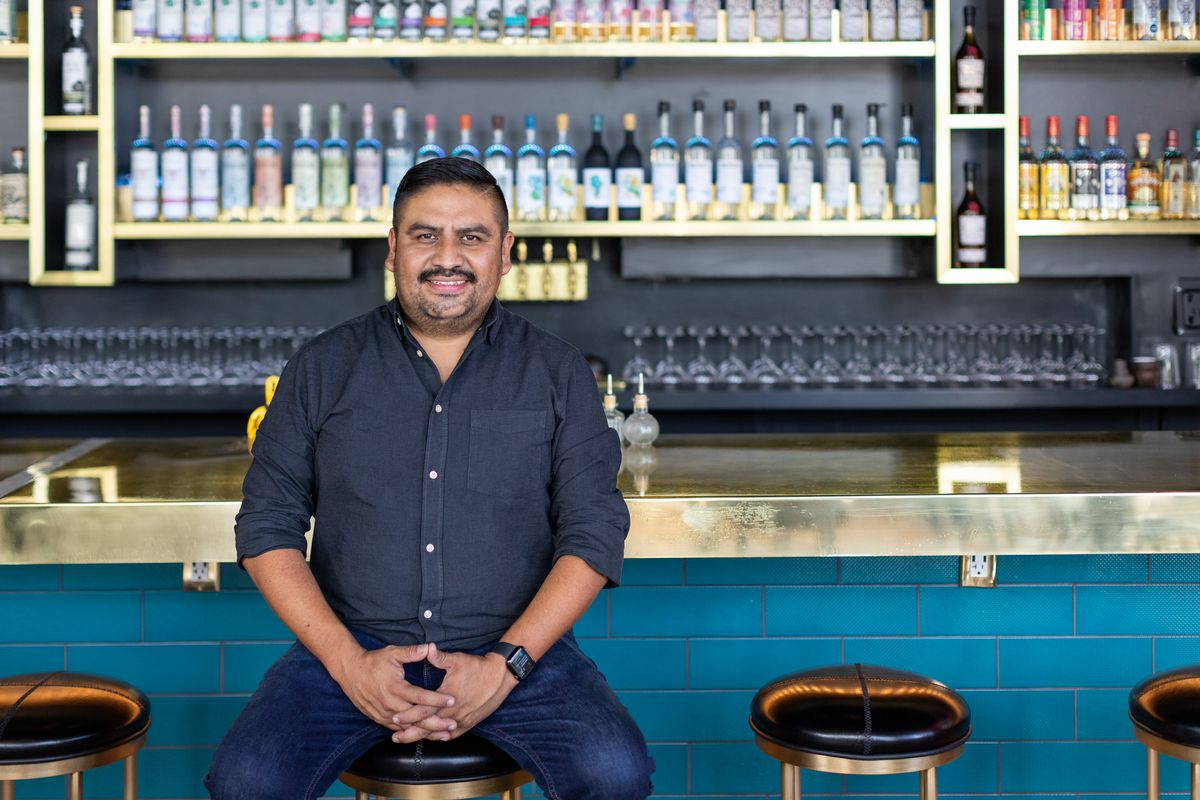 Ivan Vasquez, owner of Madre, sitting on a stool at his Oaxacan restaurant and bar