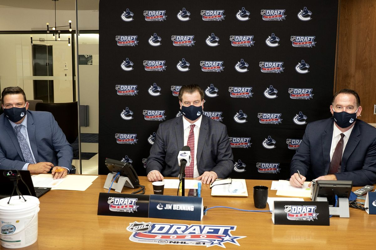 Amateur Scout Todd Harvey, general manager Jim Benning and assistant general manager John Weisbrod of the Vancouver Canucks sits at the draft table during the rounds 2-7 of the 2020 NHL Entry Draft at Bell MTS Place on October 07, 2020 in Vancouver, British Columbia, Canada. The 2020 NHL Draft was held virtually due to the ongoing Coronavirus pandemic.