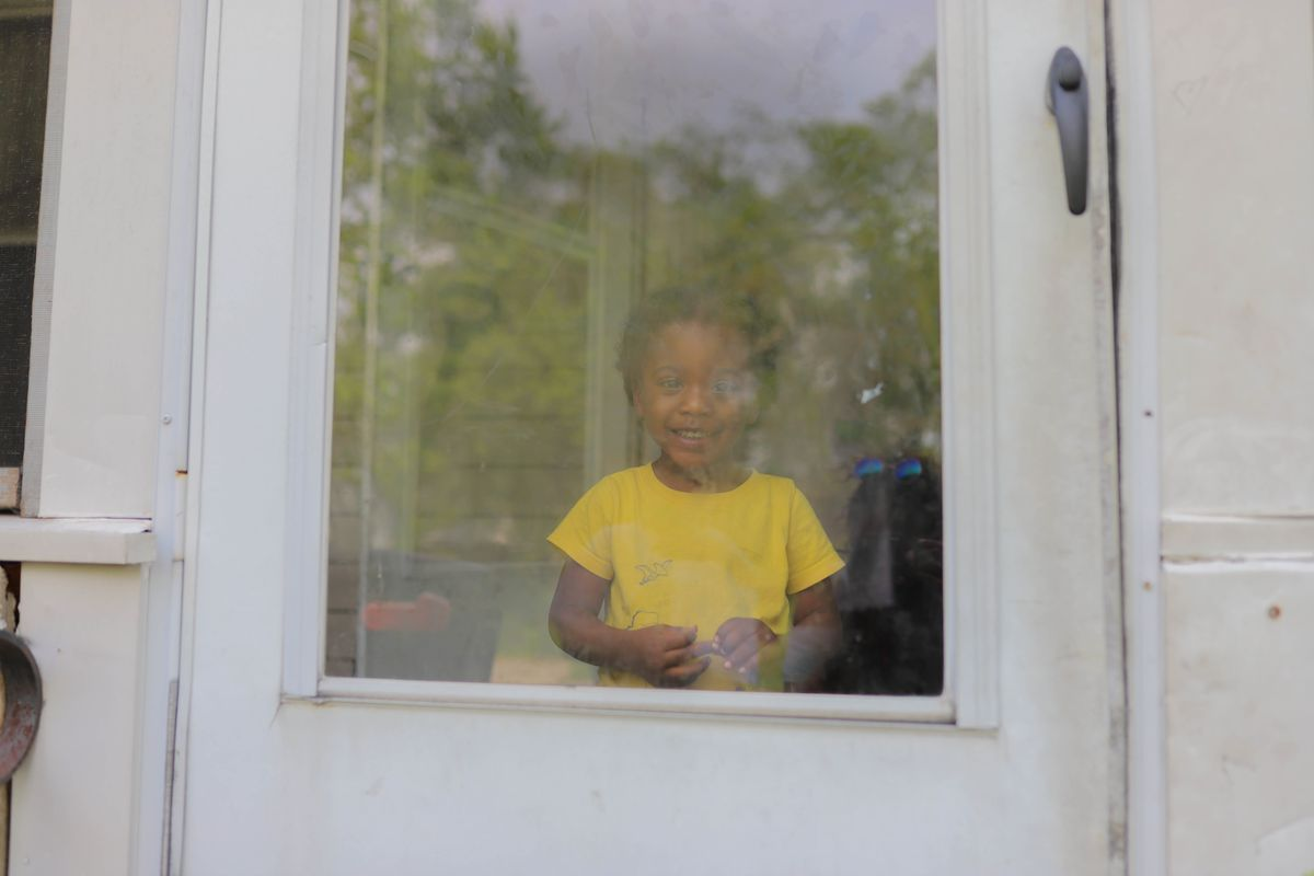 A young boy wearing a yellow shirt stands behind a pane of glass at his white front door, smiling as green trees reflect off of the glass.