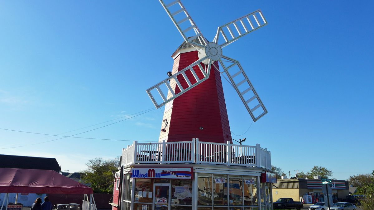A two story red building like a fakey windmill with a deep blue sky in the background.