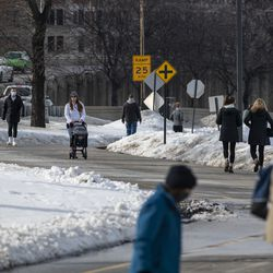 A group of people walk along the Lakefront Trail near Belmont Harbor, Tuesday, Feb. 23, 2021. The Chicago Parks District reopened the Lakefront Trail Tuesday.