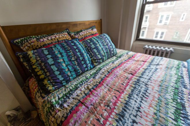 A bed with patterned bed linens and pillows.