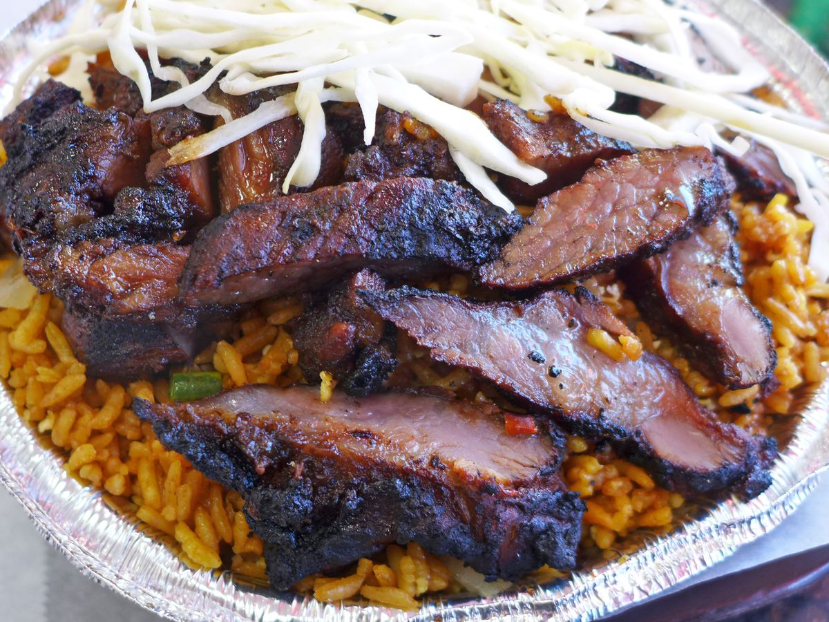 A carryout tin of orange rice topped with jerk pork and shredded cabbage.