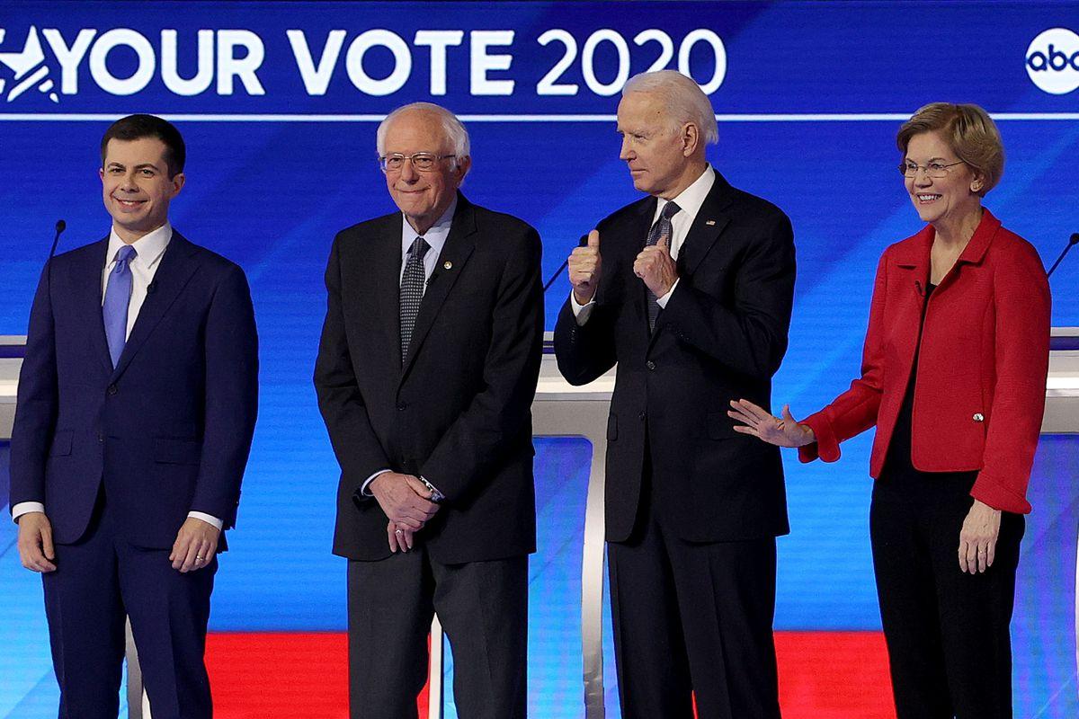 Democratic presidential candidates former South Bend, Indiana Mayor Pete Buttigieg, Sen. Bernie Sanders (I-VT), Sen. Elizabeth Warren (D-MA), and former Vice President Joe Biden, stand on stage for the Democratic presidential primary debate in New Hampshire.