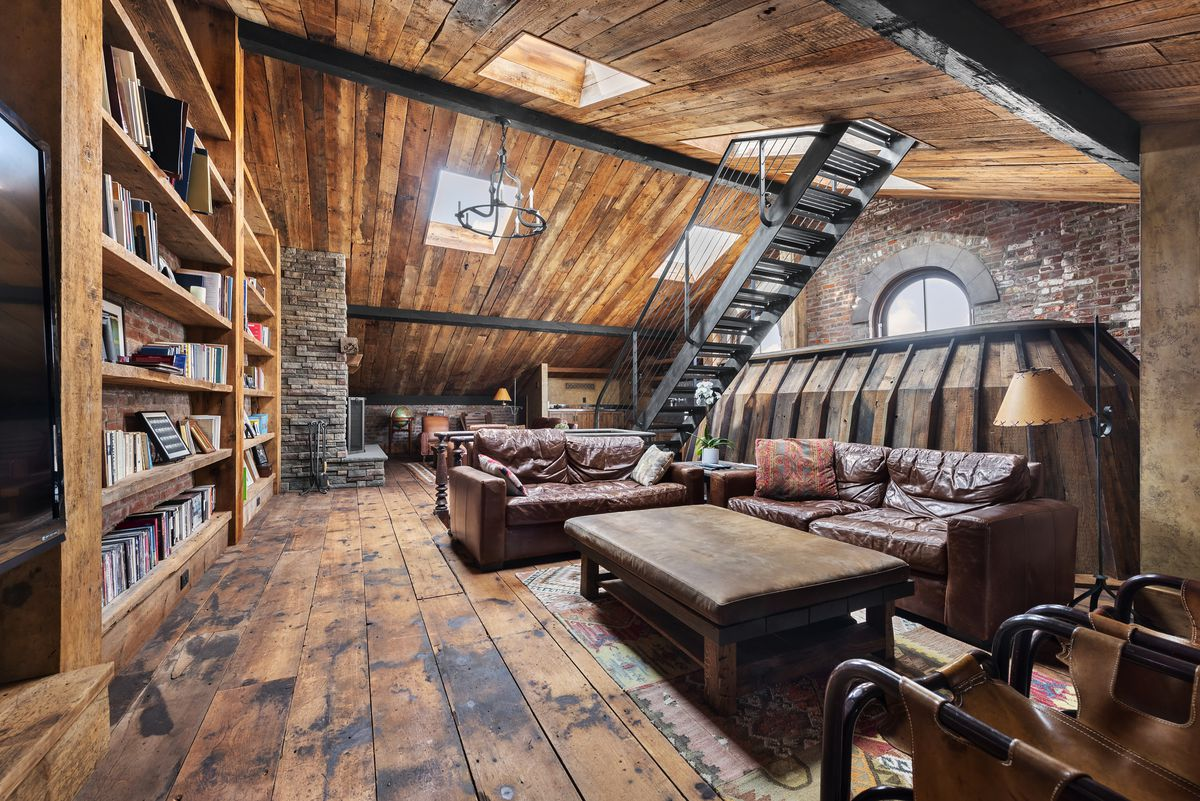 An attic with wood panels, exposed brick, two leather couches, and a large bookshelf.