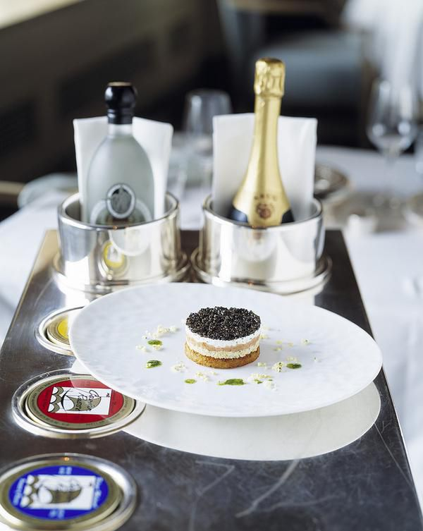 A caviar dish on a white plate with Champagne and vodka