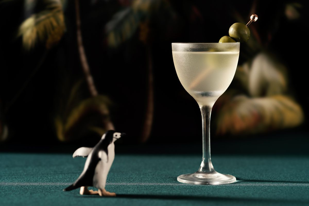 A martini with a very cute sculpture of a penguin next to it
