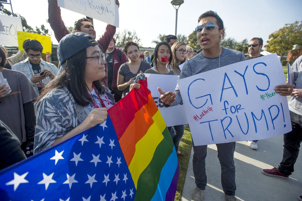 """A protester carrying a rainbow-striped American flag looks at a counterprotester carrying a sign that reads, """"Gays for Trump."""""""