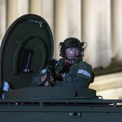 A deputy with the Kenosha County Sheriff's Office sits in the turret cupola of a bearcat telling protesters to disperse while shooting some with pepper balls during a protest over the shooting of Jacob Blake, Tuesday, Aug. 25, 2020, in Kenosha, Wis.