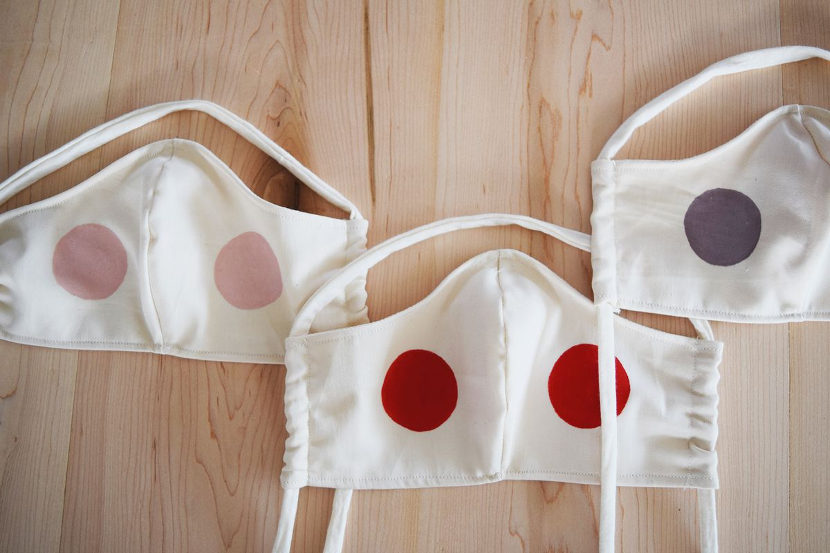 Pink, red, and mauve polka dot masks on a wooden table.