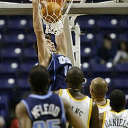 Utah Jazz's Mehmet Okur goes in for a slam over the Seattle SuperSonics.