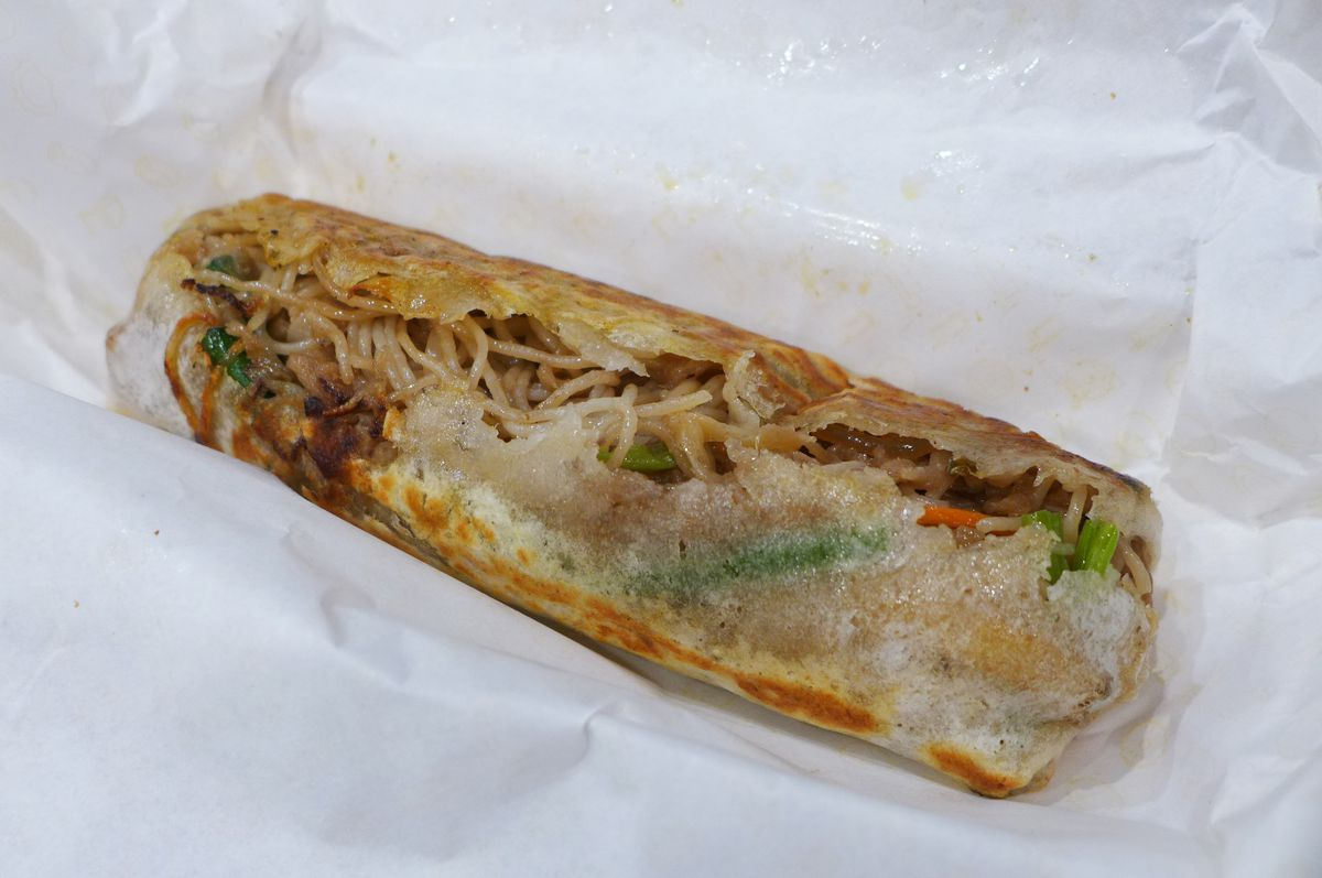 A flatbread stuffed with noodles is bursting open to show its contents...