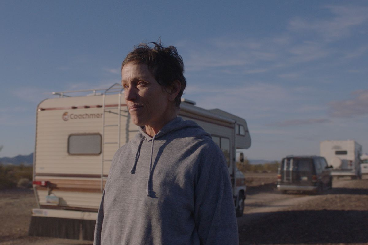 A woman wearing a hoodie stands in front of a line of RVs driving down a road.