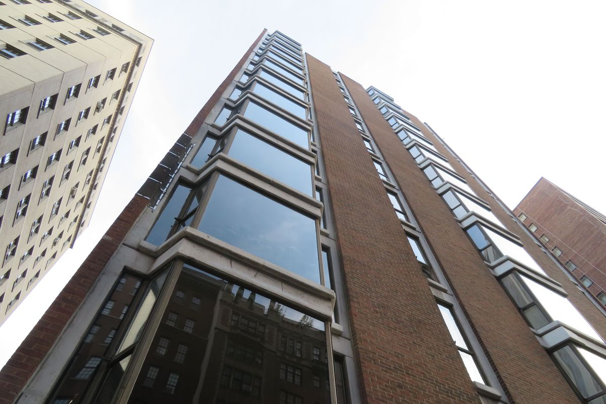 Looking up at a midcentury modern style mid-rise building with a brick facade and stacks of three-sided bay windows. The downtown building is surrounded by taller structures.
