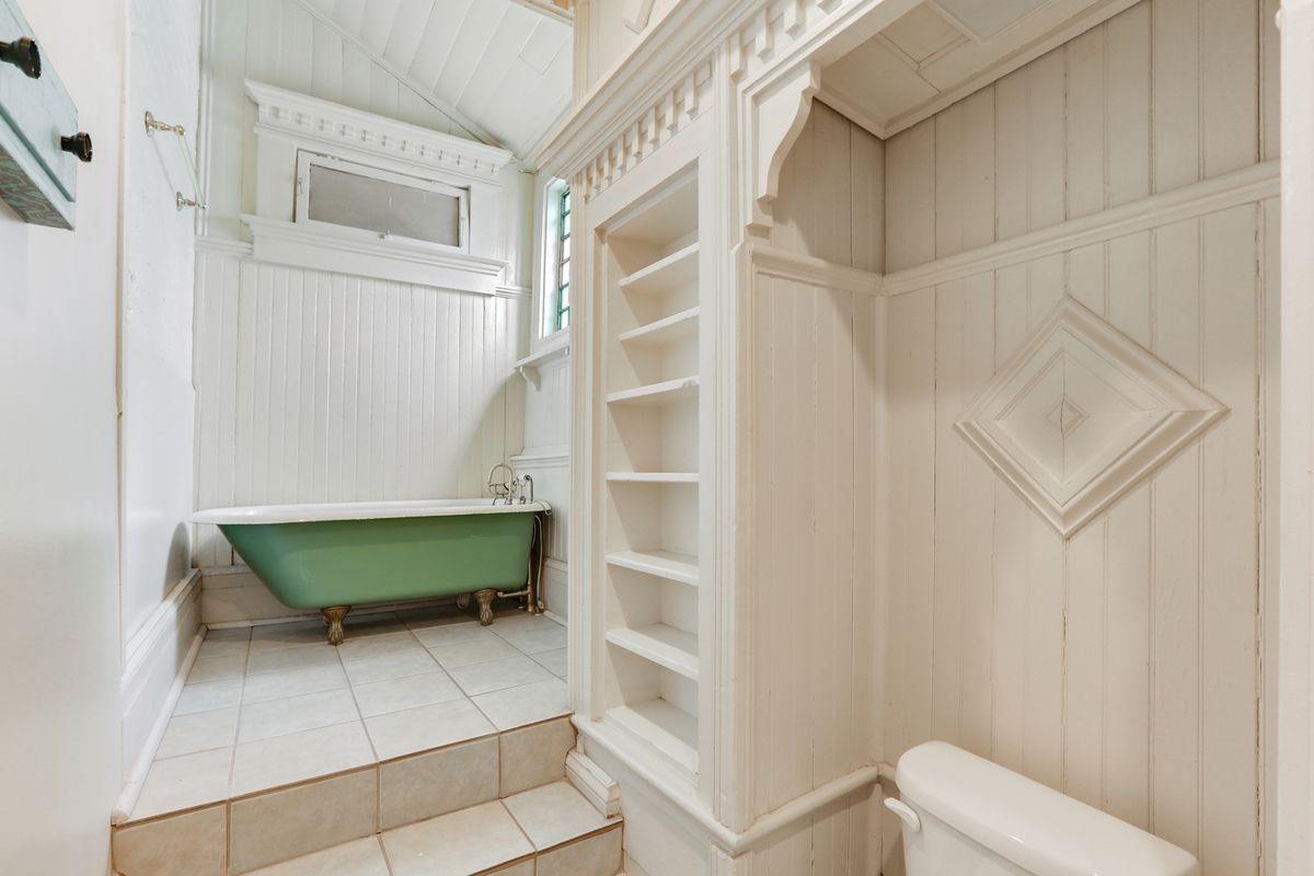 A bathroom with green clawfoot tub up a short flight of stairs and white built-in cabinetry.