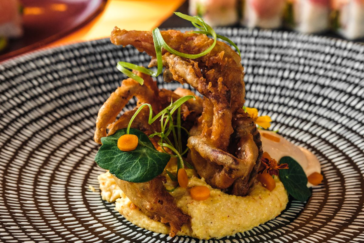 A black and white plate with soft shell crab in a sauce.