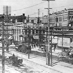 Telephone and power poles cross in every direction on Main Street and 200 South in the 1890s.