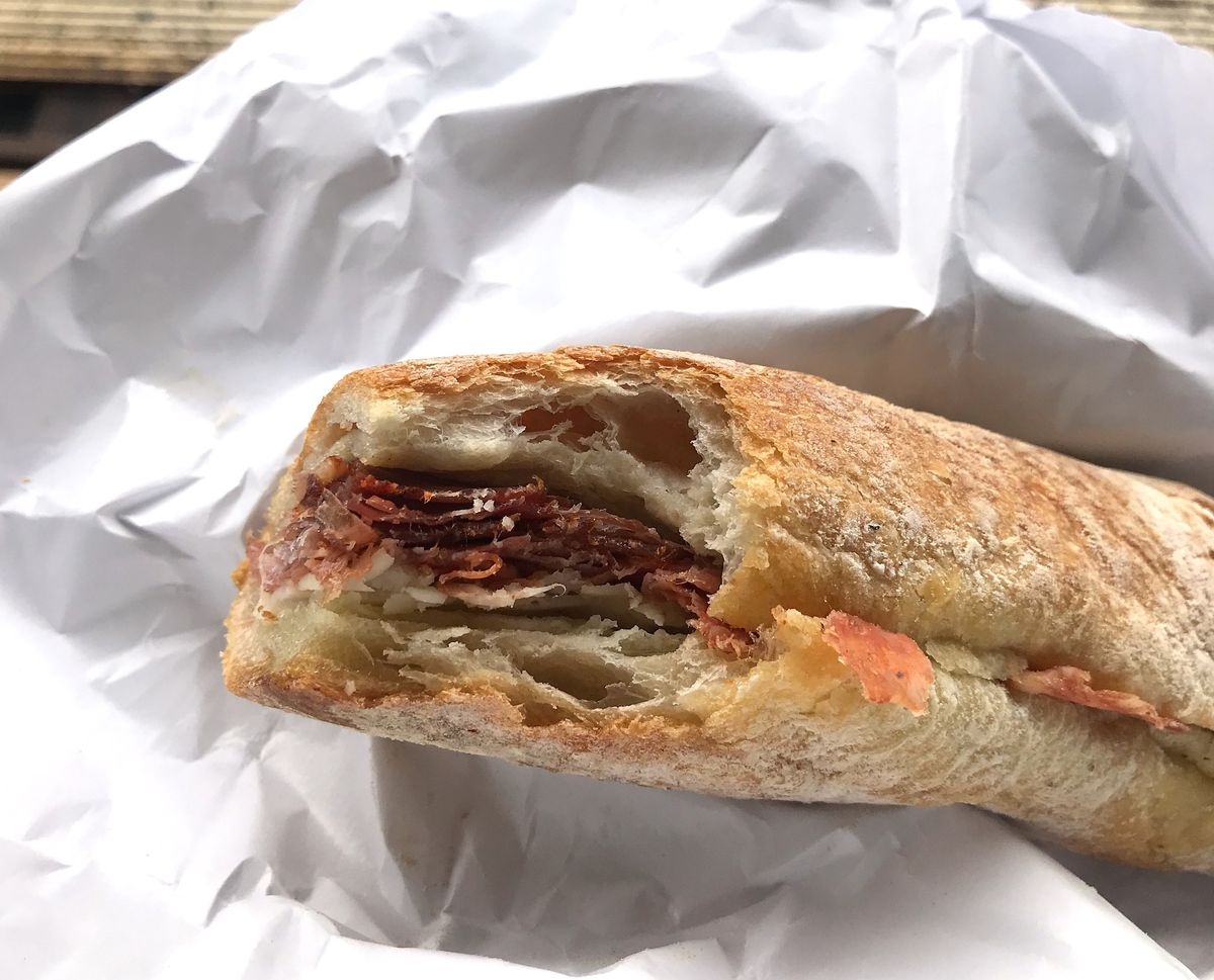 A baugette sandwich with three kinds of meat inside