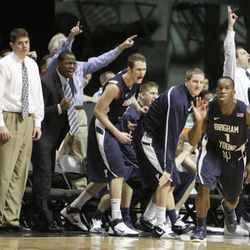 BYU\'s Charles Abouo (1), sends his bench into a frenzy, including coach Dave Rose, left, after making another three point shot during the second half of their 80-67 victory over San Diego State in an NCAA college basketball game in San Diego, Saturday, Feb. 26, 2011.