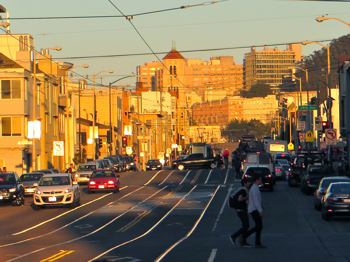 A street in San Francisco with tracks on it. There are buildings on each side of the street.
