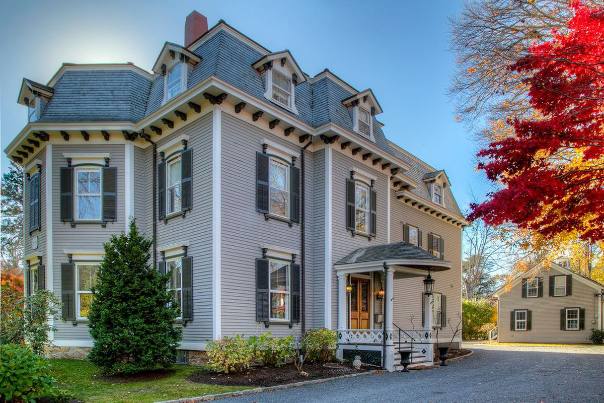 Exterior shot of grey-painted wooden Victorian home in Second Empire style with mansard roof and shutters.