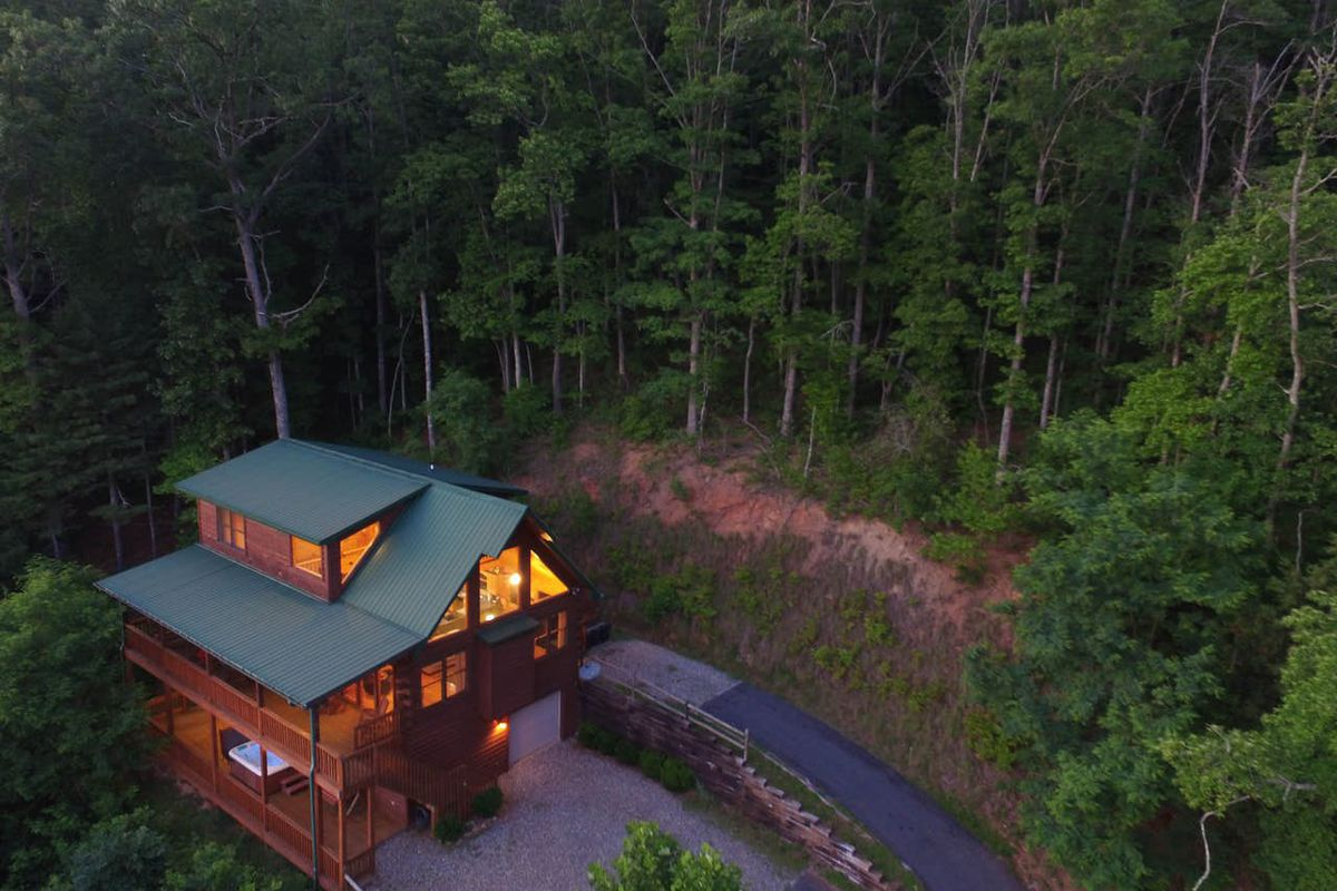 An aerial view of a wooden cabin with a green roof, porch, and lights on inside. A driveway and green forest surrounds the house.