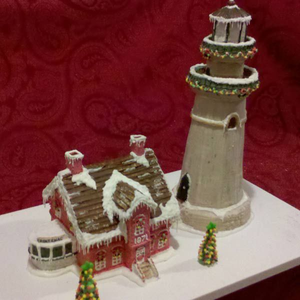Gingerbread lighthouse next to a gingerbread house.