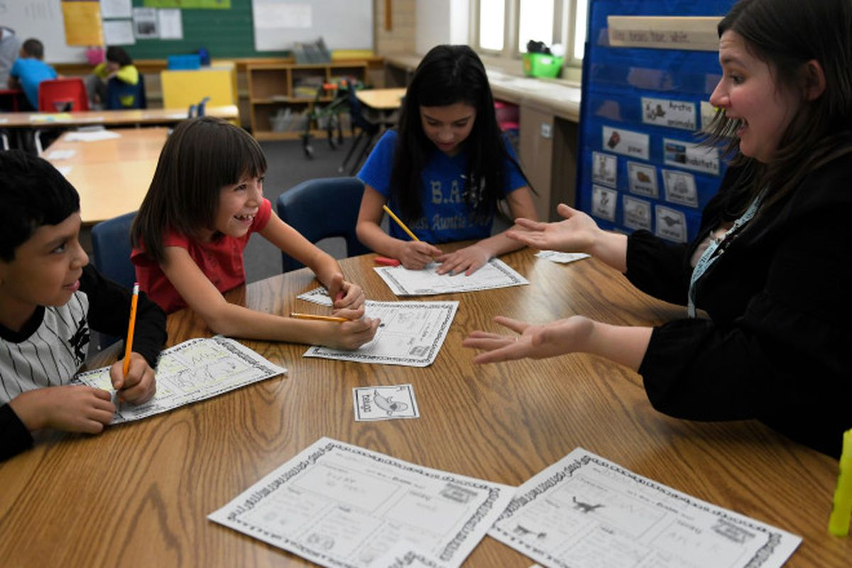 A teacher and three elementary school students sit at a table in a classroom. The teacher has a surprised look on her face, and one of the students is laughing.