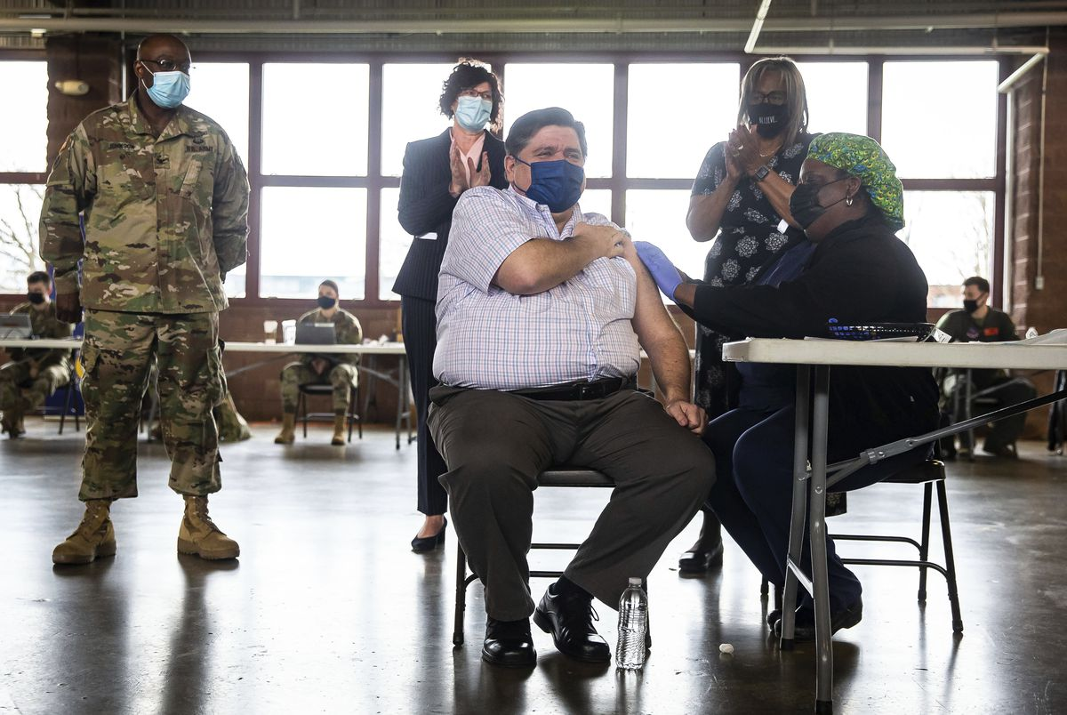 Gov. J.B. Pritzker gets a bandage after receiving the Johnson & Johnson COVID-19 vaccine in Springfield on Wednesday.