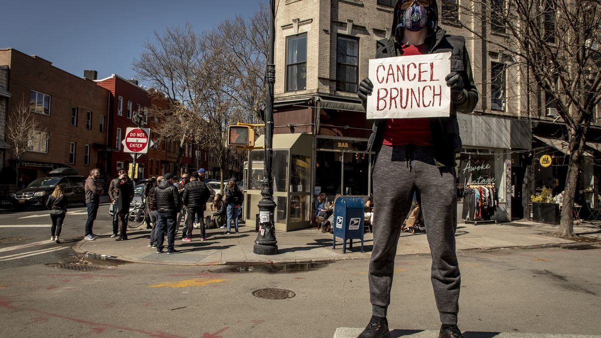 """Riley Goodside wears a mask and stands at a corner with a sign saying """"cancel brunch"""" in Greenpoint"""