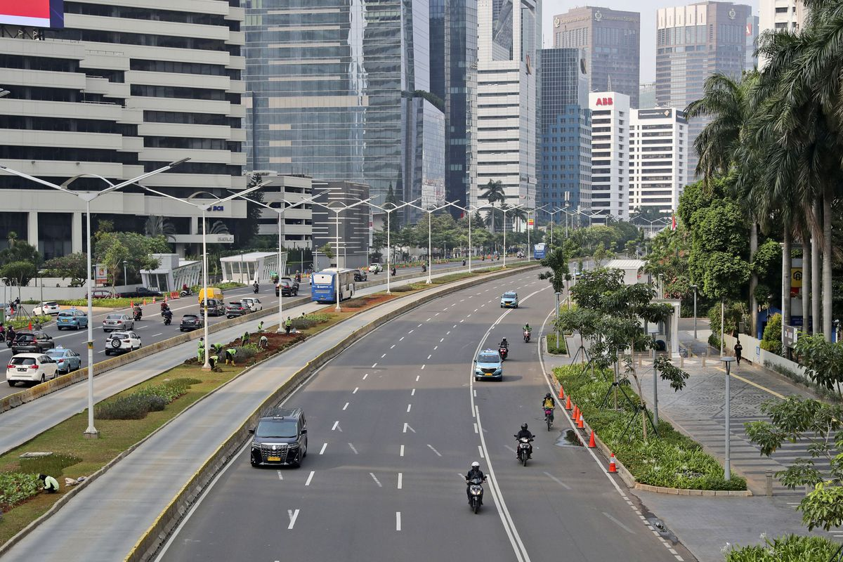 Cars and motorcycles are seen on Sudirman street that is usually busy with traffic, at the main business district in Jakarta, Indonesia, Monday, Sept. 14, 2020. Indonesia's capital on Monday begins to reimpose large-scale social restrictions to control a rapid expansion in the virus cases.