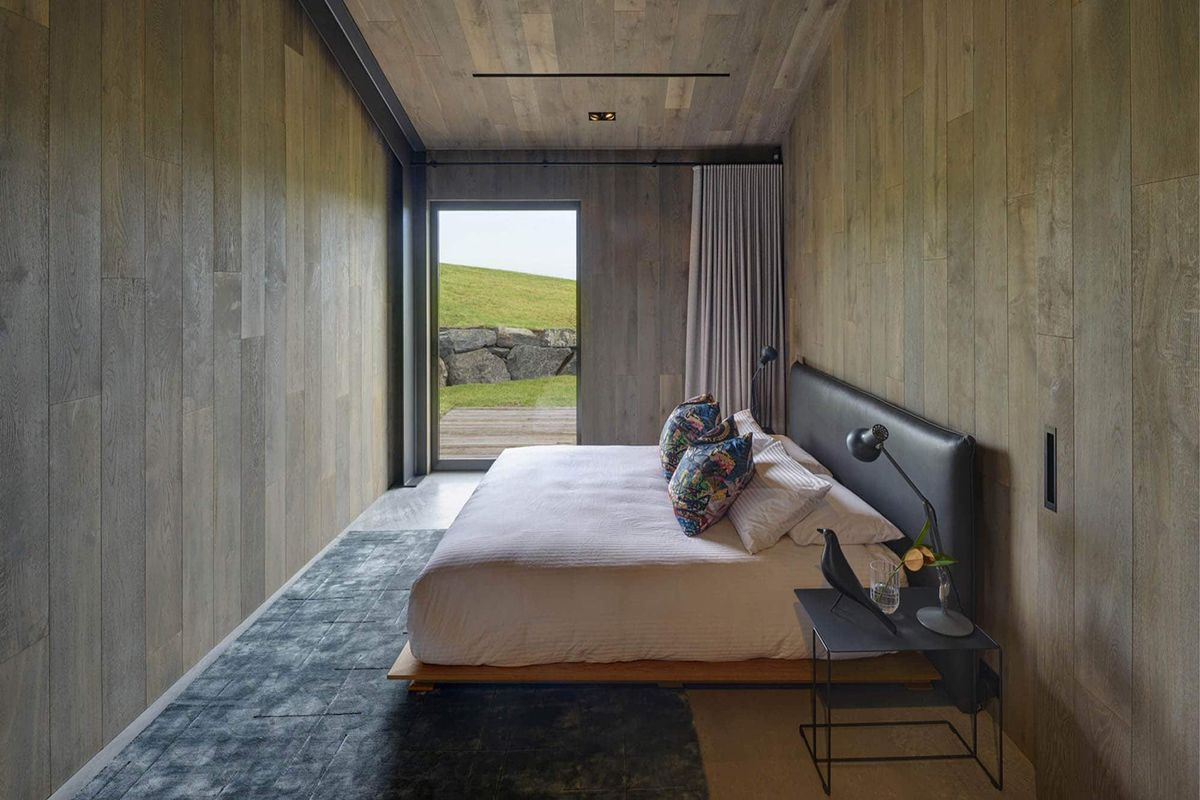A bedroom which has wooden walls, a grey floor, and a tall window. There is a bed with multiple pillows and neutral colored bed linens.