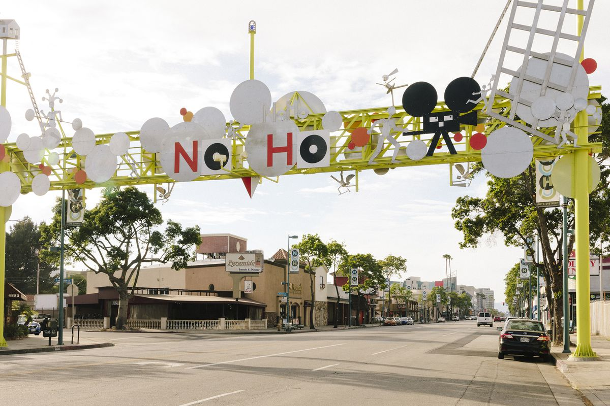 Funky yellow, white, red, and black NoHo Gateway sign spans Lankershim Boulevard. Low-slung businesses line the boulevard.