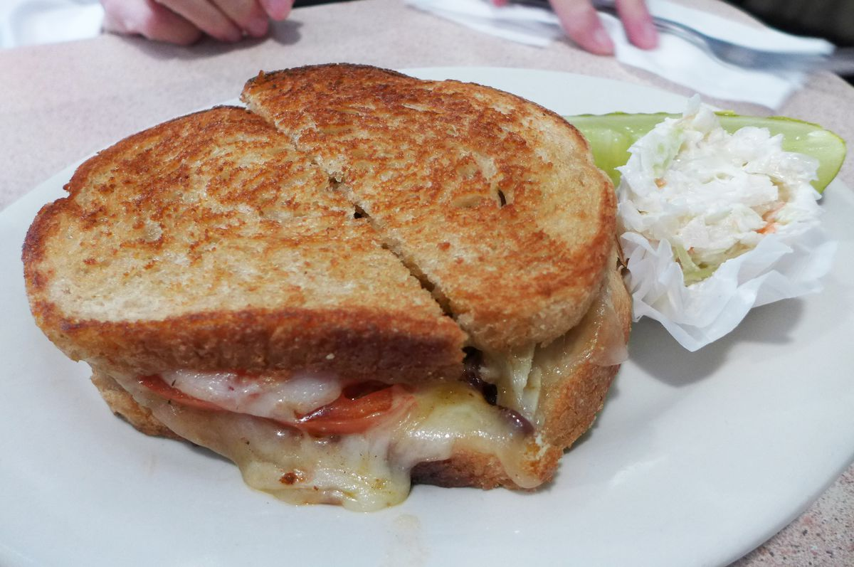 A toasted cheese sandwich is shown with cheese oozing, and a tomato slice also peeps out...