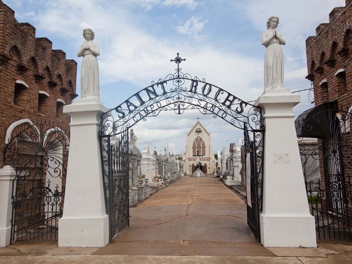 An altar area in New Orleans in Saint Roch's cemetery. There are red brick buildings on both sides of a path. There is a sign in front of the path that reads: Saint Roch's campo santo.