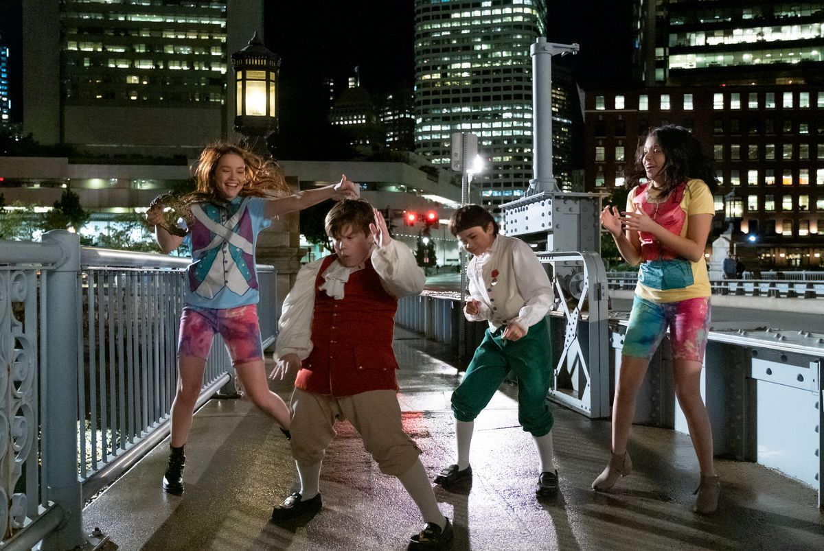 four kids in novelty clothing dance on a dock