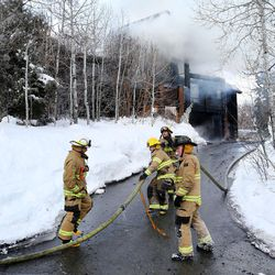 Park City firefighters extinguish a house fire in Summit Park on Wednesday, Jan. 13, 2016. Neighbors said they heard an explosion just before the home's garage burst into flames Wednesday morning.