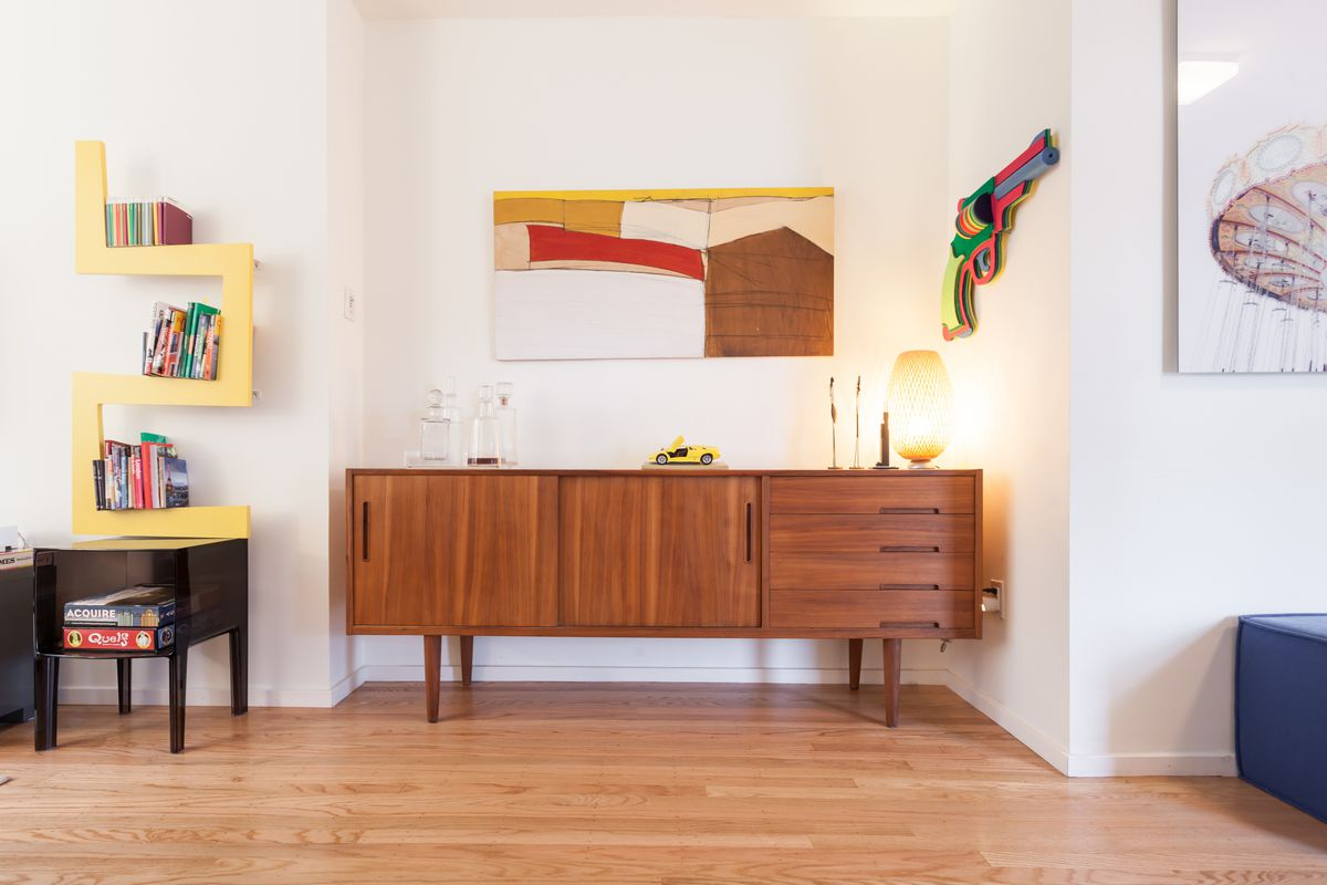 A living area with a dresser, shelves, works of art, and tables.