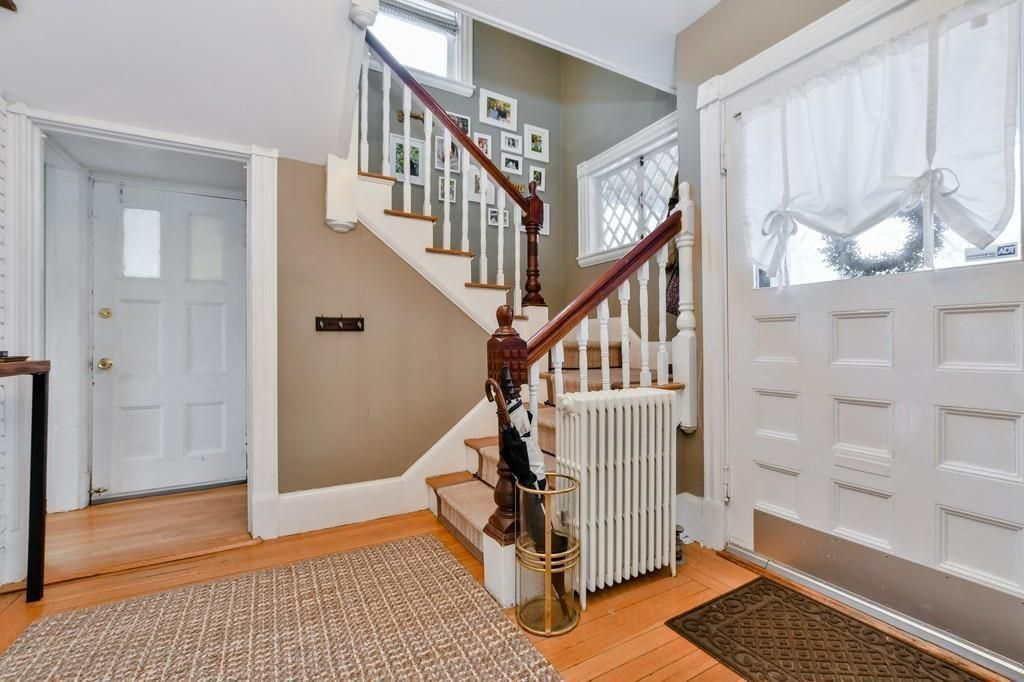 A sizable and sunny entry foyer with a staircase.