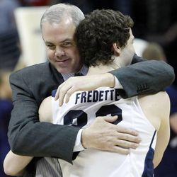 BYU coach Dave Rose hugs guard Jimmer Fredette after BYU defeated Gonzaga on March 19, 2011, in the third round of the NCAA Tournament in Denver. Fredette, now with the Sacramento Kings, is suing Utah-based clothing company Black Clover Enterprises for allegedly failing to pay him and using his name and likeness for profit.