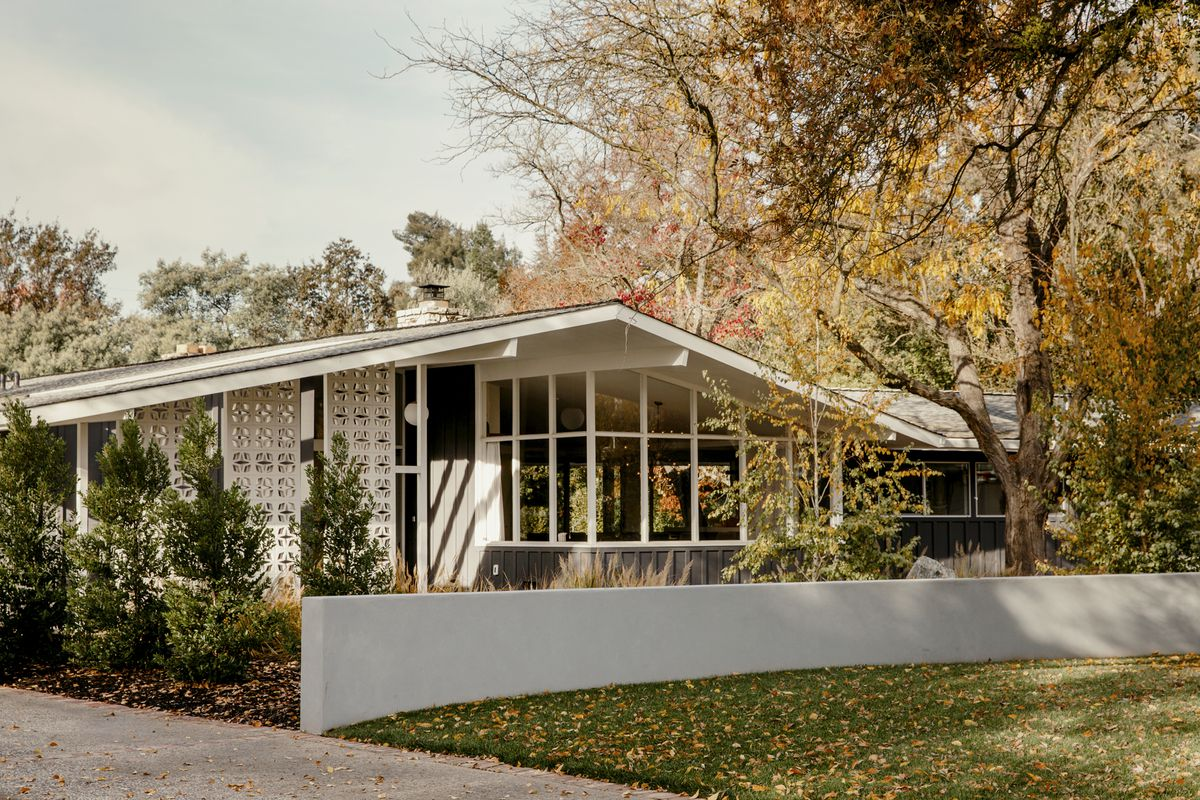 The front of the house features classic midcentury lines and elements: A low-slung gabled roof and breeze blocks.