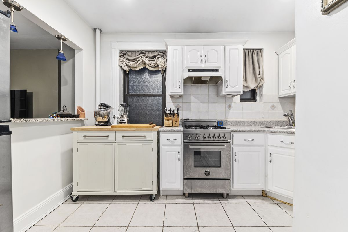 A kitchen with white cabinetry and two small windows.
